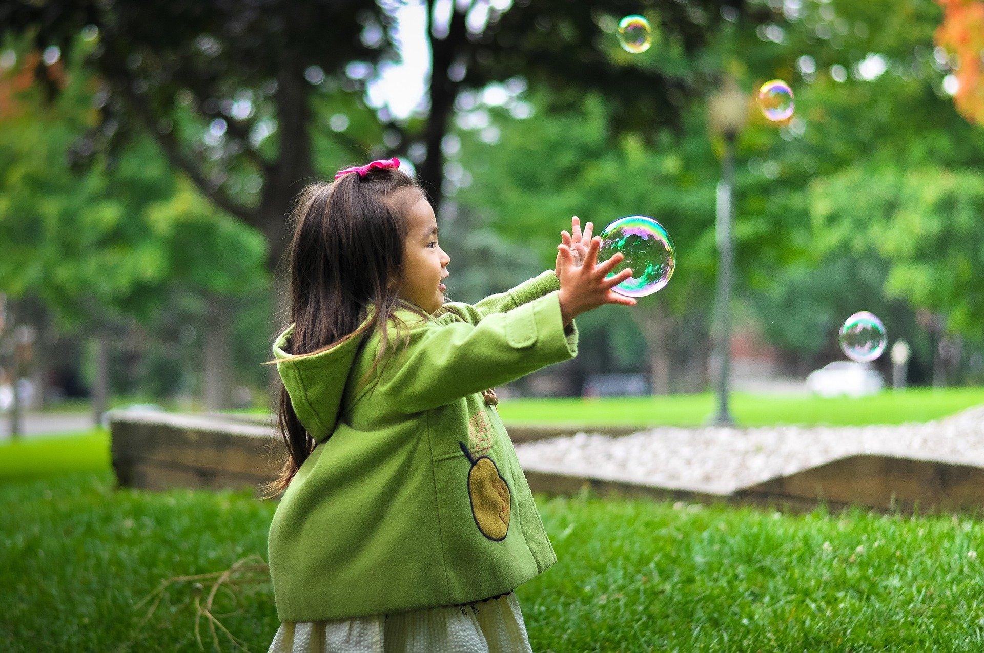 Kind_fängtSeifenblasen_DeineKinderbetreuung